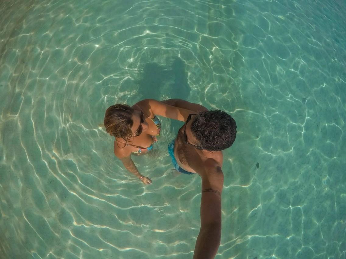 Pareja en el mar perhentian, aguas cristalinas, abrazados en traje de baño