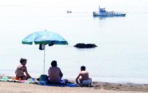 Málaga, 2 de mayo de 2007. Playa y barco recogenatas . Una familia asiste al paso por La Malagueta de una de las embarcaciones 'quita nata', ayer.¶barco quita natas. limpieza del agua del mar