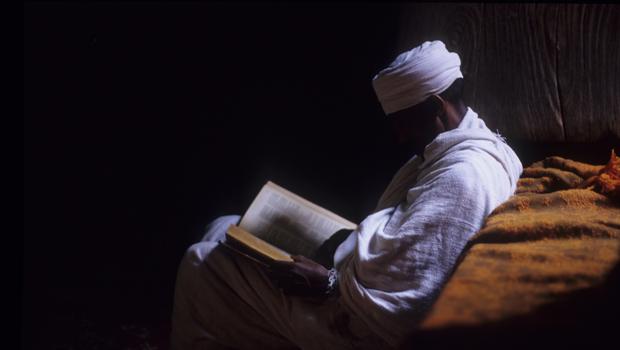Homme lisant dans la pénombre