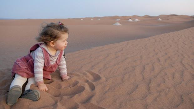 Enfant jouant dans le sable du désert