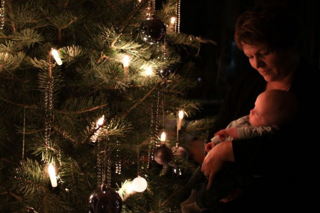 mother-holding-cute-baby-boy-against-christmas-tree-at-night-595895007-59da825b396e5a0011e878cf