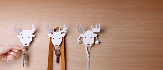 três cabides de parede em forma de animal brancos