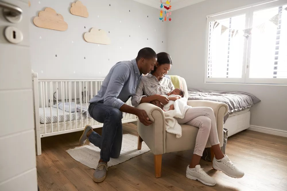 Young couple with newborn baby in small nursery
