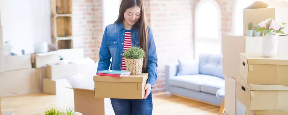 Young woman carrying boxes in new apartment