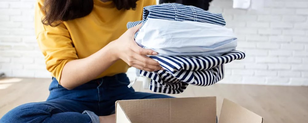 Woman putting clothing into moving box