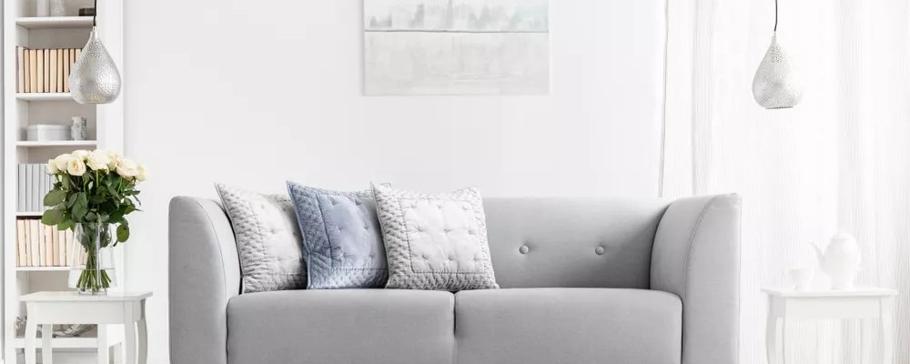 Modern gray couch in minimalist white living room