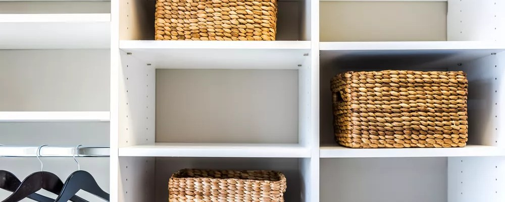 Cubbies with wicker baskets and hangers in storage closet