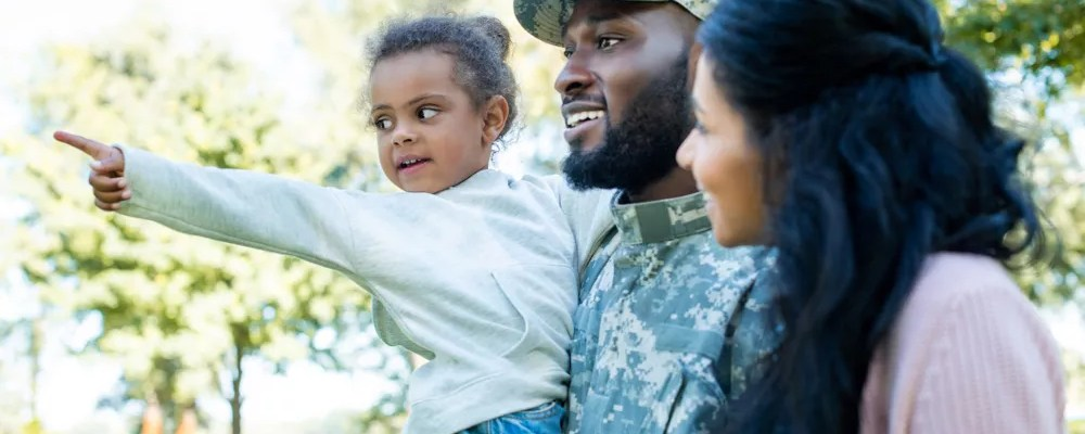 Military family standing together with little daughter pointing.