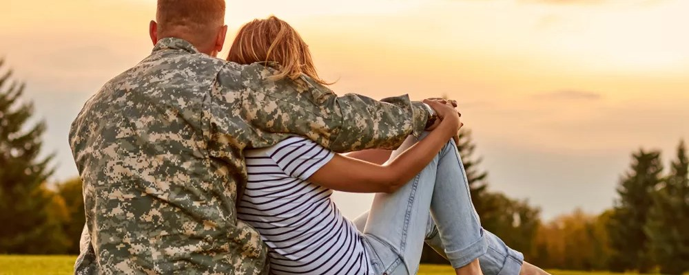 Military husband hugging his wife as the sun sets