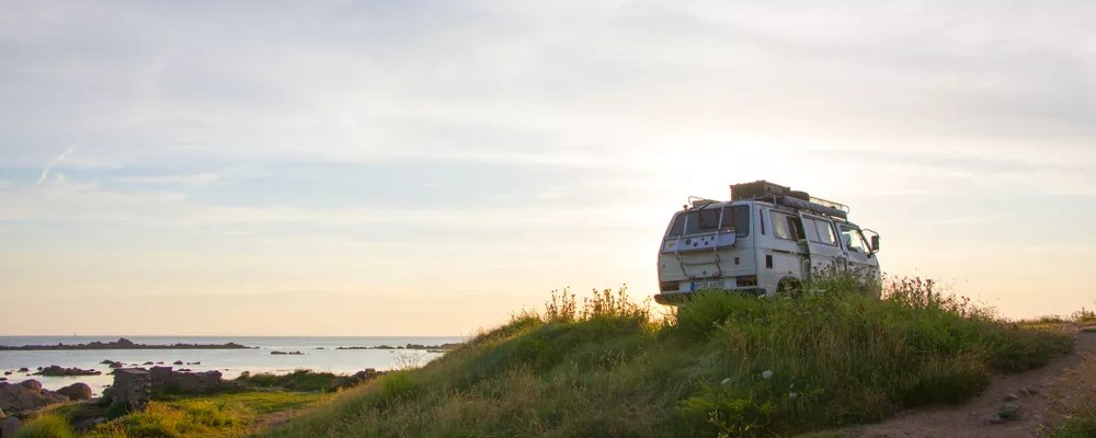 Van on a grassy hill at sunset