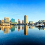 Skyline of tall buildings reflecting next to water in Baltimore