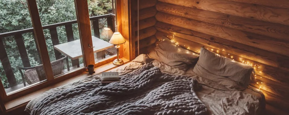Bed with gray bedding and twinkle lights around it.