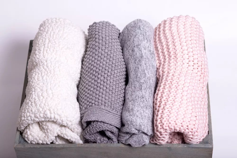 Four sweaters folded in a box
