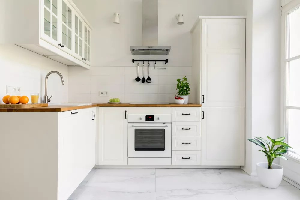 Minimalist kitchen with white walls and white cabinets.