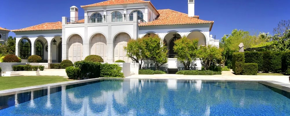 large mansion with big blue pool and perfect landscaping surrounding