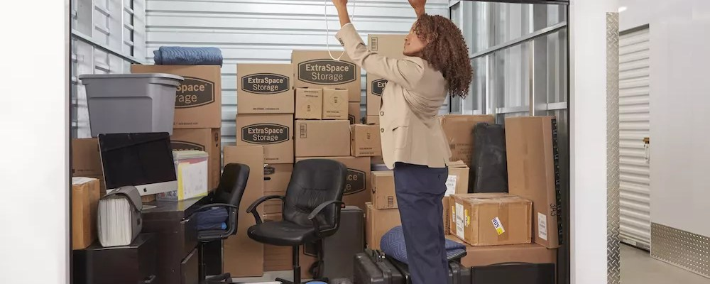 Black Woman Closing the Door of her Self Storage Unit with Boxes Inside