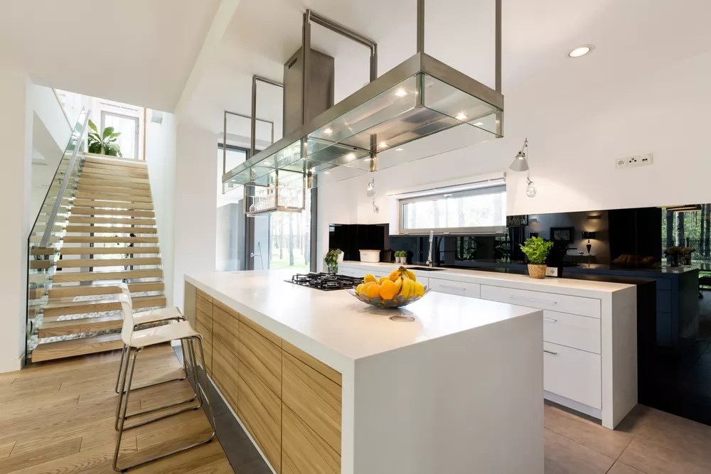 Modern white kitchen with wood accents and large kitchen island.