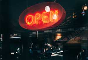 """Neon sign in window; sign says """"Open"""""""
