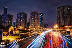 A time-lapse photo of a city and interstate at night