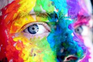 A person with vivid blue eyes and rainbow paint on their face