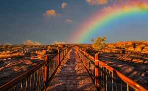 A rainbow arcs over a desert landscape with a wooden walkway