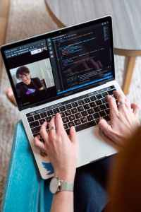 A person with a laptop does a screenshare with a person via telemeeting software
