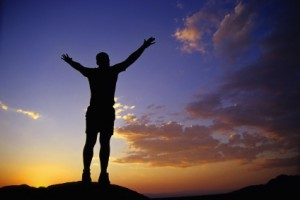 Man standing on top of a mountain with his arms up and out to the sky in victory