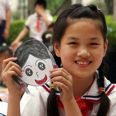 A young, smiling Asian girl with her drawn smiling-faced self-portrait