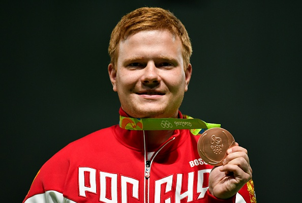 Bronze medal winner Russia's Kirill Grigoryan celebrates on the podium during the medal ceremony for the 50m rifle prone Men's Finals shooting event at the Rio 2016 Olympic Games at the Olympic Shooting Centre in Rio de Janeiro on August 12, 2016. / AFP / PASCAL GUYOT (Photo credit should read PASCAL GUYOT/AFP/Getty Images)