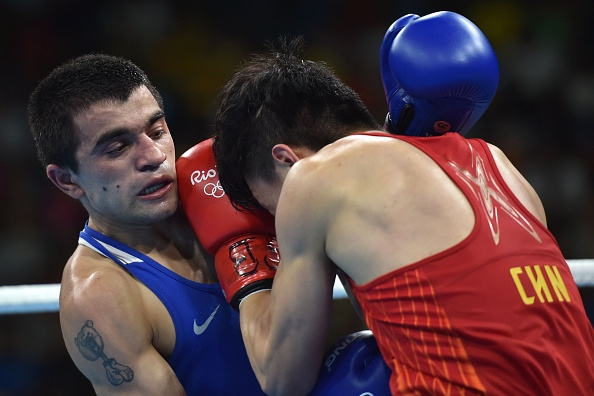 China's Hu Jianguan (R) fights Armenia's Narek Abgaryan during the Men's Fly (52kg) match at the Rio 2016 Olympic Games at the Riocentro - Pavilion 6 in Rio de Janeiro on August 15, 2016. / AFP / YURI CORTEZ (Photo credit should read YURI CORTEZ/AFP/Getty Images)