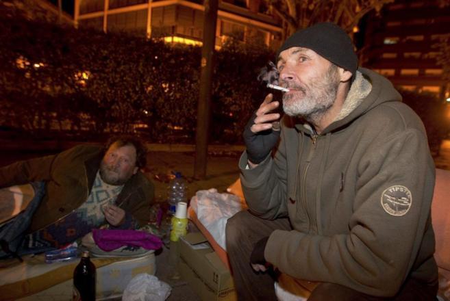 Indigentes en una calle de Valencia se disponen a pasar la noche