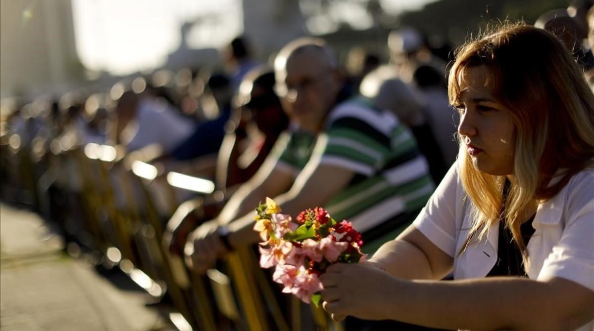 https://i2.wp.com/estaticos.elperiodico.com/resources/jpg/0/7/amanda-reyes-rodriguez-sostiene-unas-flores-mientras-espera-cola-para-despedirse-fidel-plaza-revolucion-este-martes-1480452989670.jpg