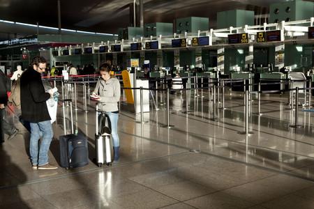 Dos jóvenes esperan para facturar en el aeropuerto de El Prat.