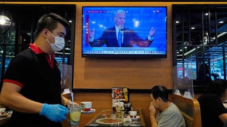 Biden ve criminal la separación de familias migrantes y Trump la defiende. En la foto, seguimiento del debate en un bar de Hong Kong.