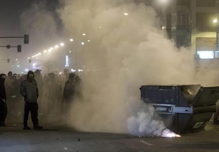 Protestantes cubiertos con pasamontañas quemando un contenedor en el barrio Gamonal.