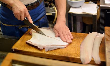 Un cocinero trabajando con un bacalao fresco.