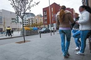 Unas mujeres en la Illa Robador, mientras dos guardia urbanos pasan ante la nueva Filmoteca, el martes.