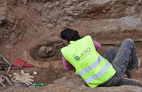 Una arqueóloga limpia uno de los esqueletos encontrados en la plaza del Pedró.