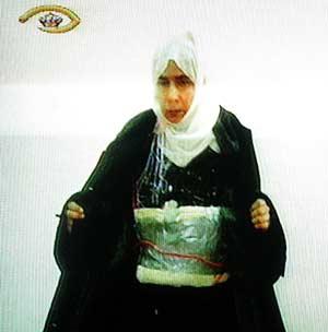 La mujer muestra el cinturón explosivo ante las cámaras. (Foto: AFP)