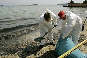 Dos operarios retiran fuel de la playa de Ses Figueretes. (Foto: EFE)