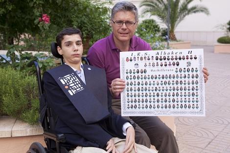 El joven Ángel López posa junto a su padre, que muestra la orla de su graduación. | M. Cubero