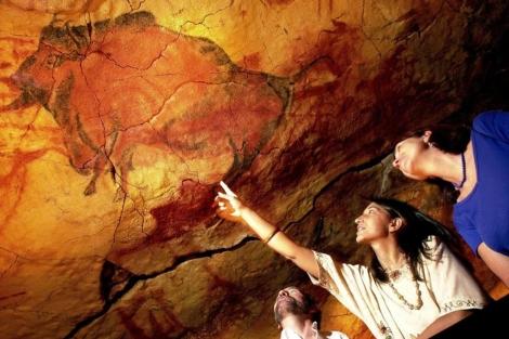 Dos turistas observan las pinturas de la cueva. | Carlos García