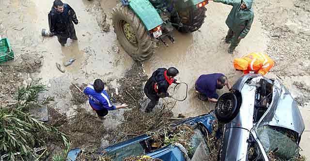 Varias personas recuperan dos vehículos atrapados en un puente de Villanueva del Rosario (Málaga). | Efe