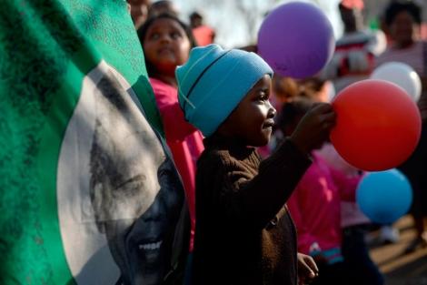 Un niño sudafricano juega con globos frente a la imagen de Mandela. | Afp
