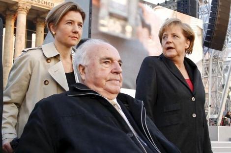 Kohl, en silla de ruedas, llevado por su mujer y acompañado por Merkel. | E.M.