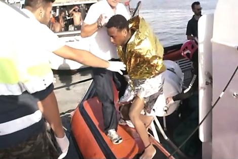 La guardia costera ayuda a un inmigrante a desembarcar. | Afp
