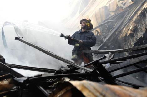 Un bombero trata de apagar el fuego en la fábrica textil. | Reuters