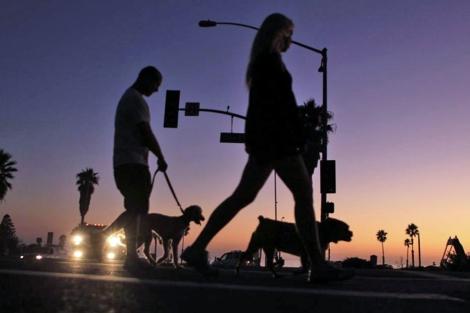 Una pareja pasea a sus perros casi a oscuras en Cardiff, California. | Reuters