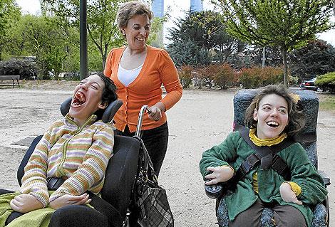 Ana García pasea por Madrid con sus dos hijas, María (dcha.) de 20 años y Clara, de 25, con de parálisis cerebral