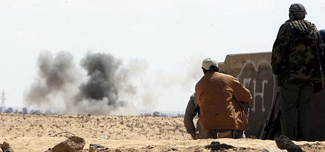 Rebeldes libios observan el humo de los combates en la carretera que une Ajdabiya y Bengasi. | Efe